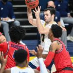 UTC basketball player shoots while guarded by Samford players.