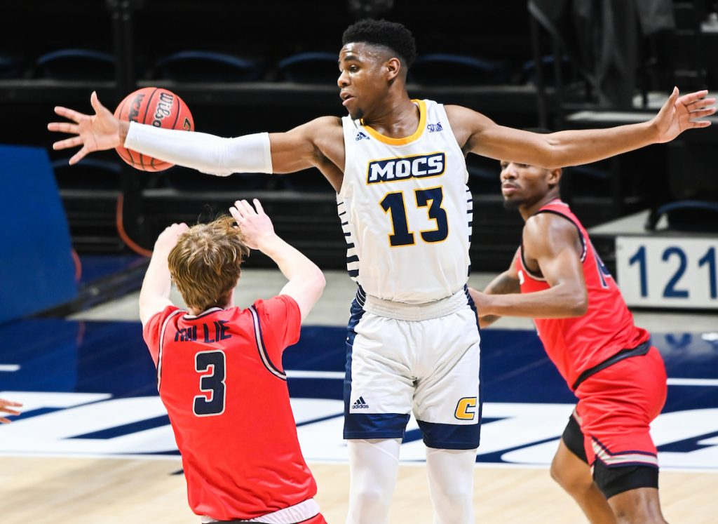 UTC basketball player reaching for basketball while guarded by Samford players.