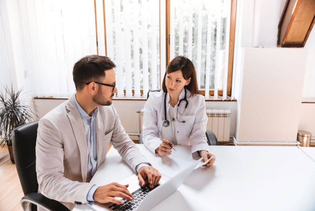 A medical doctor and a business person sit at a table with a laptop computer.