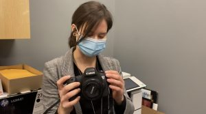 Amy is wearing a medical mask and is holding a camera while taking a mirror selfie.