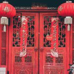 Large red wooden doors with red paper tapestries and lanterns hanging in front. One on each side.