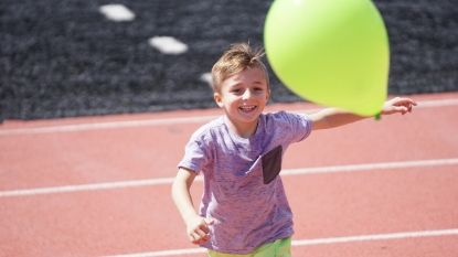 a small boy playing with a green balloon