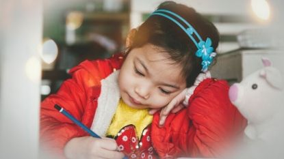 a young girl drawing with a pencil