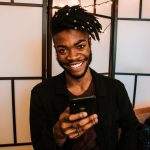 man smiling while holding his cell phone