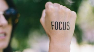 the word focus written on a woman's hand