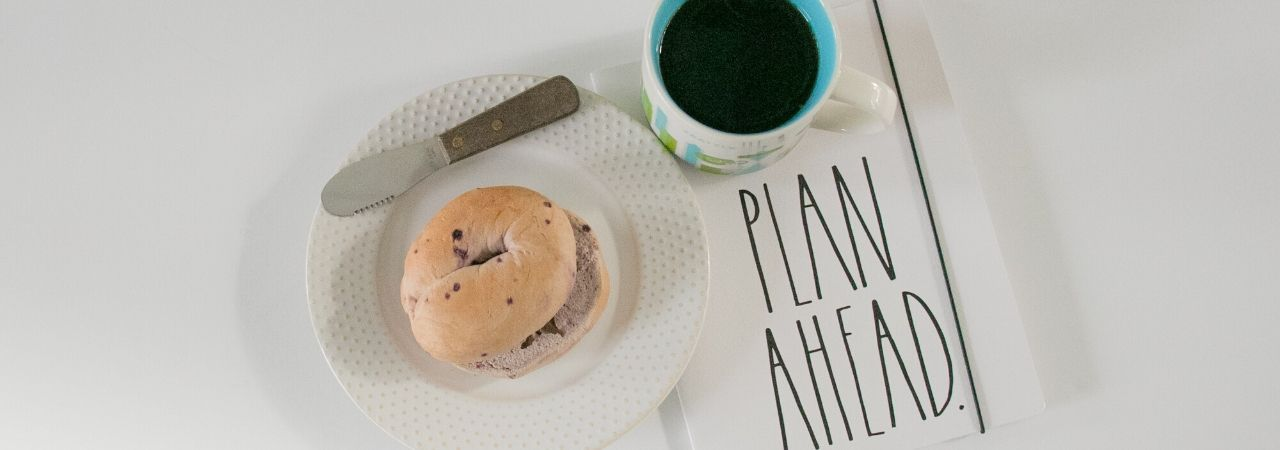 a cup of coffee, a planner, and a bagel
