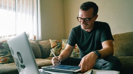 man working on his laptop and iPad from home