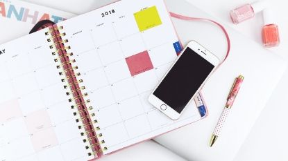 white iPhone and planner on a desk