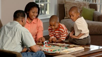 African-American family playing Monopoly together