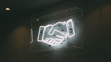 a neon sign of shaking hands