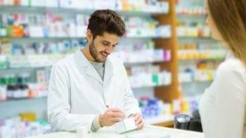 male pharmacy tech giving a prescription to a customer