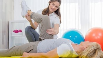 female physical therapy aide stretching out a patient