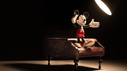 Mickey Mouse standing on top of a piano with a spotlight on him