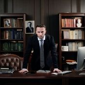 a man leaning over the top of his desk with an intense face