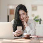 woman smiling looking at her phone by her laptop