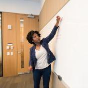 female teacher writing on a white board