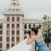 female travel photographer taking photos at a monument