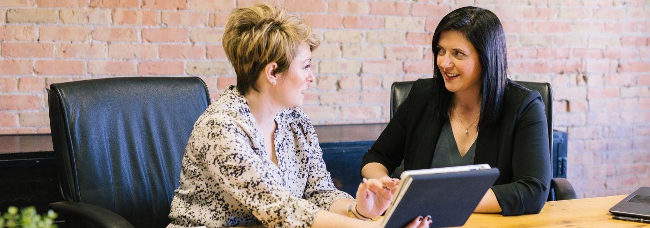 two women speaking in an office
