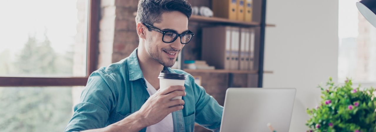 man drinking coffee and looking at his laptop