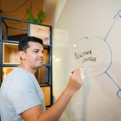 male creating a strategy on a white board