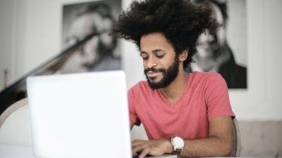 man smiling while typing on his laptop