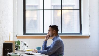 man staring intensely at a laptop computer