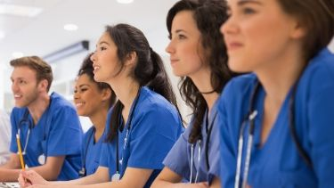 students in blue scrubs listening to an instructor talk