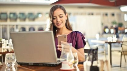 woman looking at her phone with her laptop open