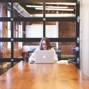 woman staring at a laptop intently in an office by herself