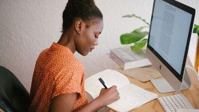 woman taking notes while sitting in front of her desktop computer