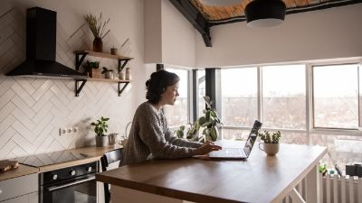 woman working on a laptop sitting at her kitchen island countertop