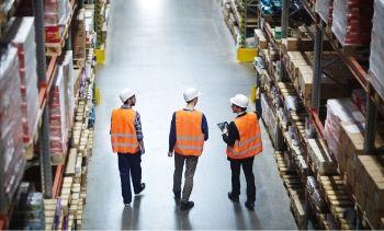 3 men wearing construction gear walking through a warehouse