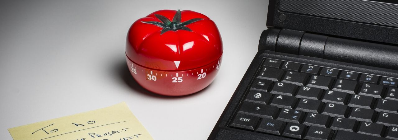 a tomato timer sitting between a black laptop and a to do list