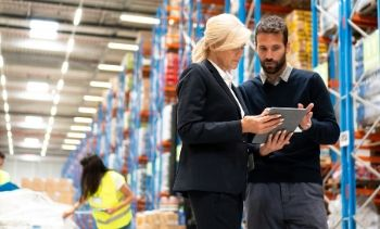 businessman and businesswoman looking at a tablet in a warehouse