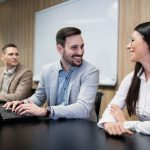 business professionals in a meeting room with camera focused on smiling young man