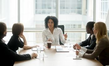 female leading in white shirt leading an office meeting with team members all wearing black