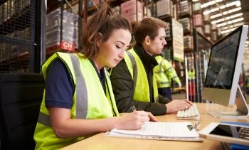 man and woman managing warehouse logistics in an on-site office