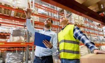 man in construction gear and man in business wear walking through a warehouse