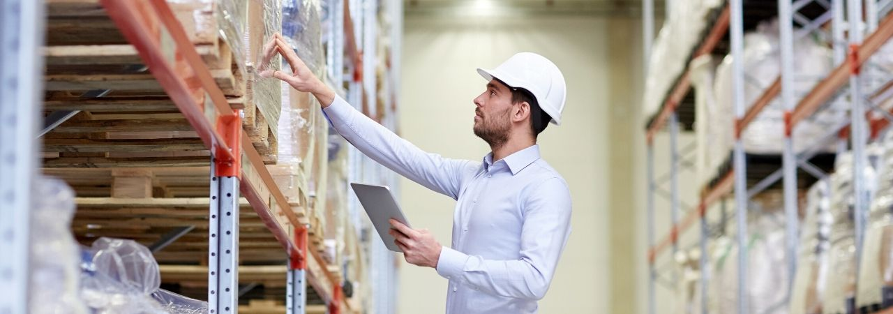 man in hard hat checking inventory in a warehouse using a tablet