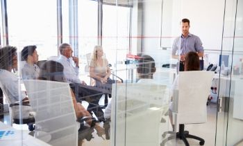 man leader standing up talking to his team members who are sitting down in a conference room