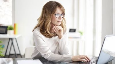 woman intently staring at her laptop