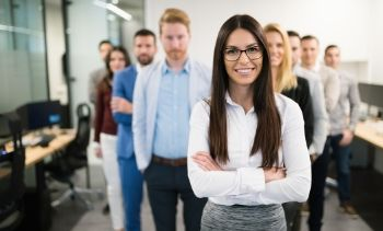 woman leader standing in front of her team in the office