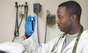 A black man African American doctor holding a test tube vial sample of blood