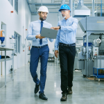 two male supply chain workers looking at a laptop while walking through a warehouse