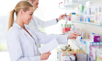 female and male phamacists placing medicine on shelves