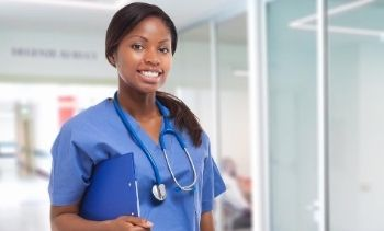 female medical assistant smiling in scrubs holding clipboard