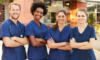 four members of a medical team smiling wearing blue scrubs