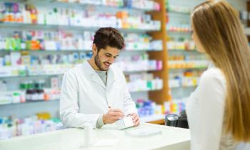 male pharmacist writing a prescription for a female customer