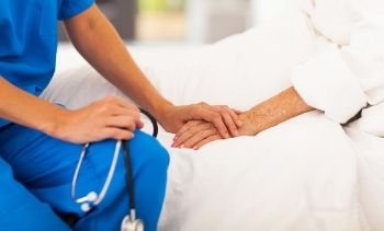 medical assistant holding a senior patient's hand in their hospital bed