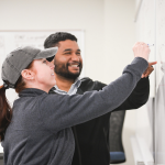 female and male student working on whiteboard together